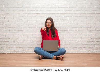 Young brunette woman sitting on the floor over white brick wall using laptop pointing with finger to the camera and to you, hand sign, positive and confident gesture from the front