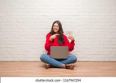 Young brunette woman sitting on the floor over white brick wall paying holding dollars very happy pointing with hand and finger