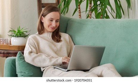 Young brunette woman sitting on couch and doing project on laptop in cozy living room at home