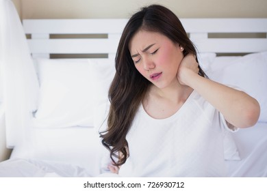Young brunette woman sitting on bed at home after wake up in the morning with neckache. Suffering from pain and Injury concept.