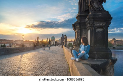 Young brunette woman, sitting relaxed on the Charles Bridge walls, over the Vltava river, admiring the sunrise over Prague City, in Czech Republic.