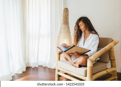 Young brunette woman sitting in wooden bamboo chair indoors and reading book or magazine. Eco style interior concept. Wicker handmade lamp behind.