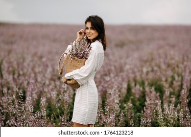 Young brunette woman standing in a big field with pink sage in bloom, holding a wicker bag with flowers.