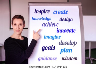 young brunette woman standing at flipchart with buisiness oriented words on it
