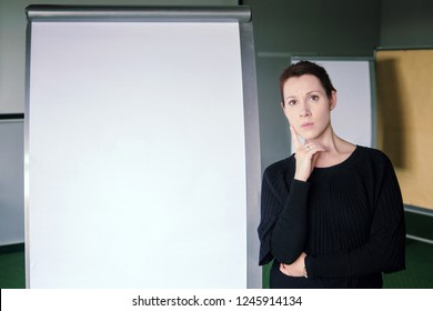 young brunette woman standing next to a flipchart in office