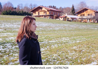 young brunette woman standing outdoors on a snowy field