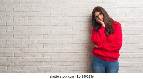 Young brunette woman standing over white brick wall thinking looking tired and bored with depression problems with crossed arms.