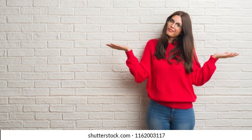Young brunette woman standing over white brick wall clueless and confused expression with arms and hands raised. Doubt concept.