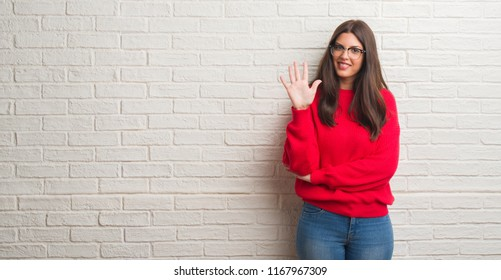 Young brunette woman standing over white brick wall showing and pointing up with fingers number five while smiling confident and happy.