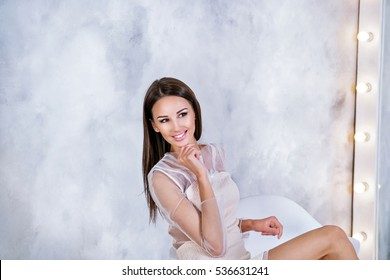 Young Brunette woman with straight and silky hair sitting in front of mirror on grey background looking on the left and smiling