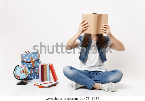 Young brunette woman student in denim clothes covering face with book read sitting near globe, backpack, school books isolated on white background. Education in high school university college concept