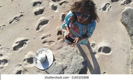 Young brunette woman in sunglasses controls piloting drone copter using console holding phone at ocean beach. Smart girl operates fly quadcopter. Travel concept technology