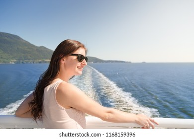 Young brunette woman in sunglasses on a ferry boat looking towards Howe Sound