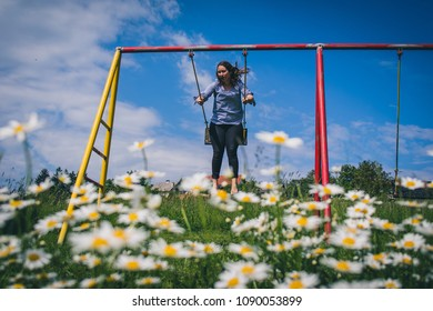 Young brunette woman is swinging on a swing, with a field of daisies (anthemidae) in the foreground on a beautiful spring sunny day. Concept of natural playfulness outdoor.
