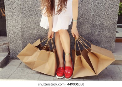 Young brunette woman with tanned slim legs in red patent leather shoes and a lot of brown paper bags her hands. Shopaholic woman in the city. The concept of shopping, sales and purchases of things.
