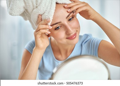 A young brunette woman with a towel wrapped round her head  examining her face in the round mirror