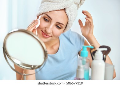 A young brunette woman with a towel wrapped round her head cleansing her skin with a cotton pad