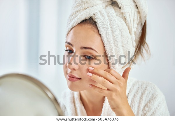 丸い鏡で顔を見ながら、頭にタオルを巻いた若いブルネットの女性