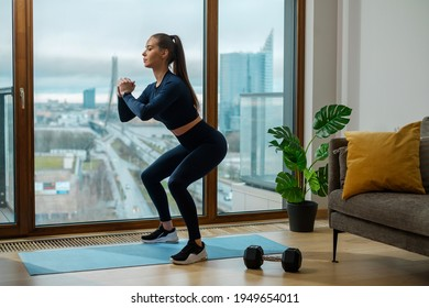 Young brunette woman in tracksuit with brown ponytail stands in squat position by lodge panoramic window with summer city outside