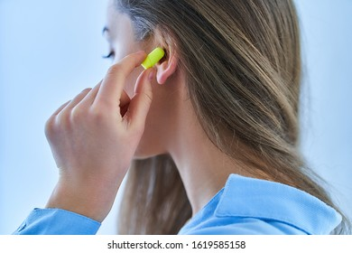 Young brunette woman using earplugs for noise protection