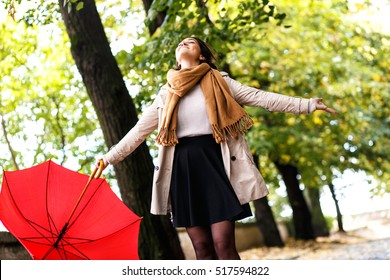 Young brunette woman walking with a red umbrella on the stone path.