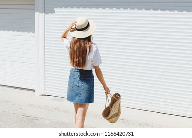 Young brunette woman wearing blue denim mini skirt, white t-shirt, wicker straw bag and boater hat walking near white roller door. Trendy casual summer or spring outfit. Street fashion. Back view.
