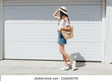 Young brunette woman wearing blue denim mini skirt, white t-shirt, sneakers, wicker straw bag, boater hat walking near white roller door. Trendy casual summer or spring outfit. Street fashion.