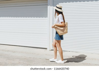 Young brunette woman wearing blue denim mini skirt, white t-shirt, sneakers, wicker straw bag, boater hat walking near white roller door. Trendy casual summer or spring outfit. Street fashion. No face