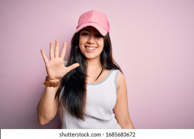 Young brunette woman wearing casual sport cap over pink background showing and pointing up with fingers number five while smiling confident and happy.
