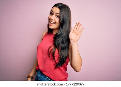 Young brunette woman wearing casual summer shirt over pink isolated background Waiving saying hello happy and smiling, friendly welcome gesture