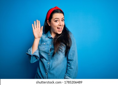 Young brunette woman wearing casual denim shirt over blue isolated background Waiving saying hello happy and smiling, friendly welcome gesture