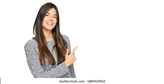 Young brunette woman wearing casual winter sweater cheerful with a smile of face pointing with hand and finger up to the side with happy and natural expression on face