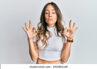 Young brunette woman wearing casual white t shirt relaxed and smiling with eyes closed doing meditation gesture with fingers. yoga concept.
