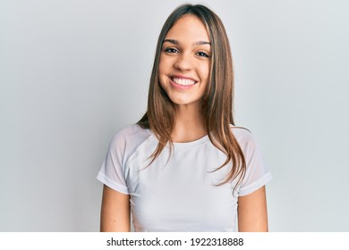 Young brunette woman wearing casual white t shirt with a happy and cool smile on face. lucky person.