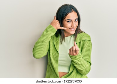 Young brunette woman wearing casual clothes smiling doing talking on the telephone gesture and pointing to you. call me.