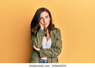 Young brunette woman wearing casual clothes over yellow background thinking looking tired and bored with depression problems with crossed arms.