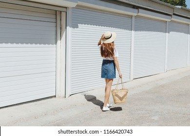 Young brunette woman wearing denim mini skirt, white t-shirt, sneakers, wicker straw bag, boater hat walking near white roller door. Trendy casual summer or spring outfit. Street fashion. Back view.