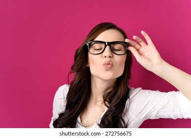 Young Brunette Woman Wearing Eyeglasses with Black Frames Puckering Lips with Eyes Closed, Blowing Kiss Towards Camera