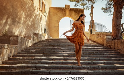 young brunette woman wearing a floral pattern summer dress, walking down a staircase, at a castle in Artà on Mallorca