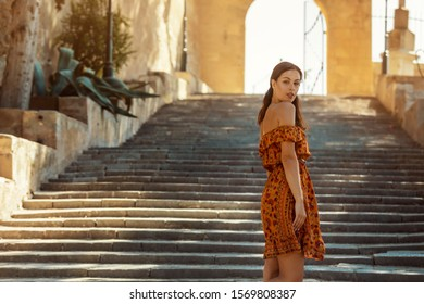 young brunette woman wearing a floral pattern summer dress, standing on a staircase, at a castle in Artà on Mallorca