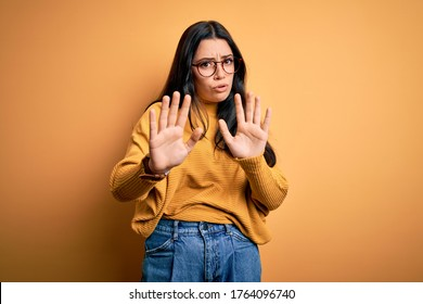 Young brunette woman wearing glasses and casual sweater over yellow isolated background Moving away hands palms showing refusal and denial with afraid and disgusting expression. Stop and forbidden.