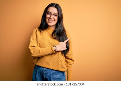 Young brunette woman wearing glasses and casual sweater over yellow isolated background cheerful with a smile on face pointing with hand and finger up to the side with happy and natural expression