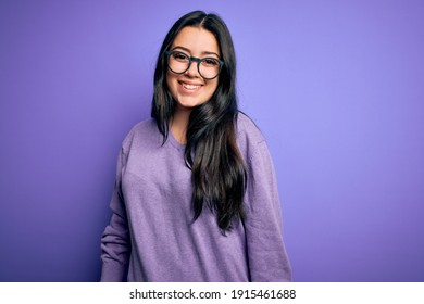 Jeune femme brune portant des lunettes sur fond violet isolée avec un sourire heureux et frais sur le visage. Heureux.