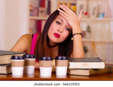 Young brunette woman wearing pink top sitting by desk with stack of books placed on it, resting head onto hand, tired facial expression, student concept