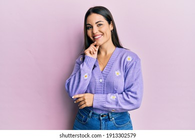 Young brunette woman wearing spring cardigan with flowers print smiling looking confident at the camera with crossed arms and hand on chin. thinking positive.