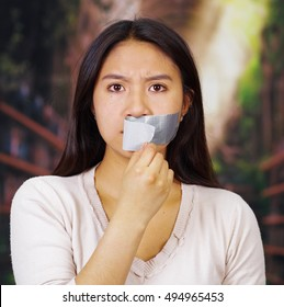 Young brunette woman wearing white taking off duct tape covering mouth, facing camera, hostage concept