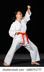A young brunette woman in a white kimono doing karate on a black background in full growth.