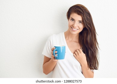 Young brunette woman in white t-shirt drinking from blue mug with both hands, looking at camera with a friendly smile. Standing against white wall with copy space.