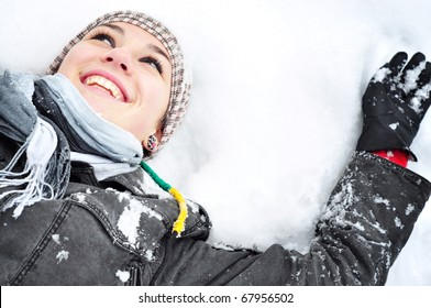 Young brunette woman with winter outfit lying on snow making snow angel.