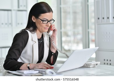 young brunette woman working at office